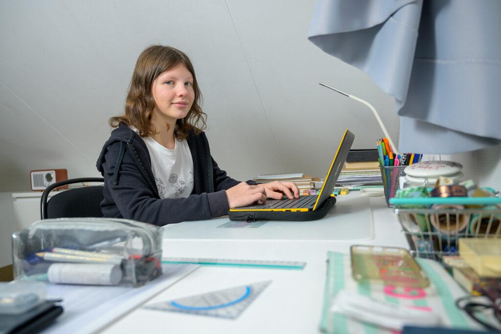 Tiener maakt huiswerk op haar slaapkamer