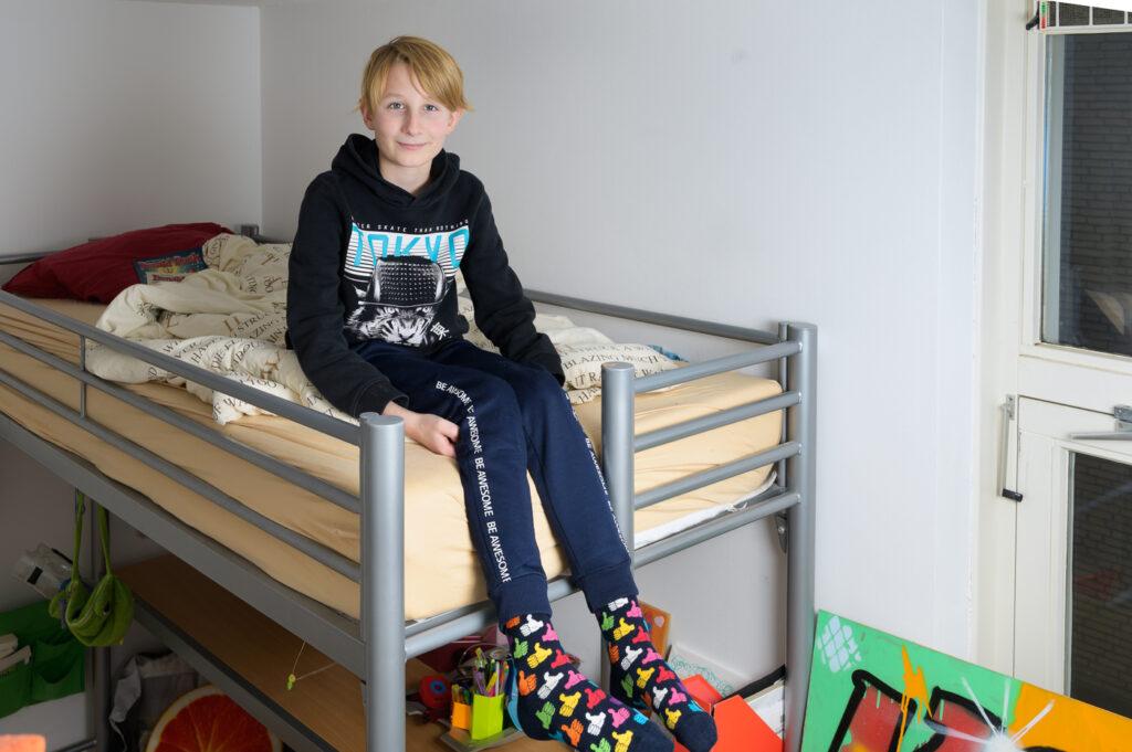 Tiener jongen zittend op bed