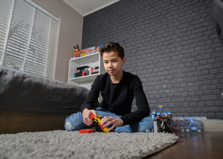 Tiener spelend met zijn lego