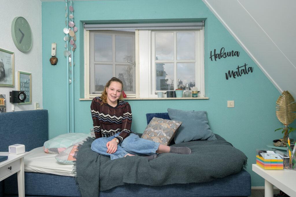 Tiener meisje zittend op bed