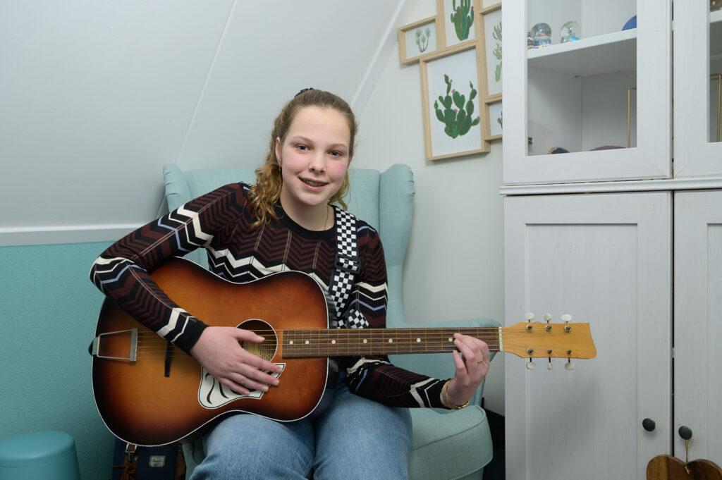 Tiener met haar gitaar op haar slaapkamer