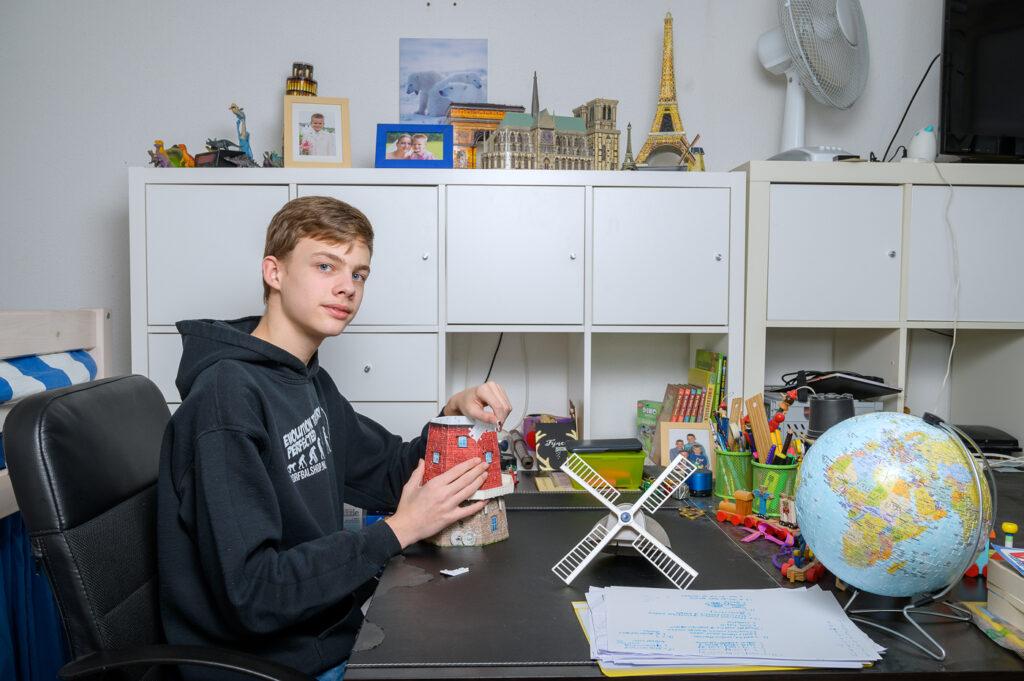 Tiener met 3D puzzels op zijn slaapkamer